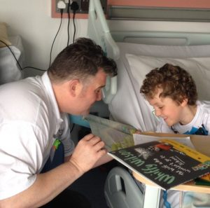 Steve Lally storytelling to a patient at his bedside